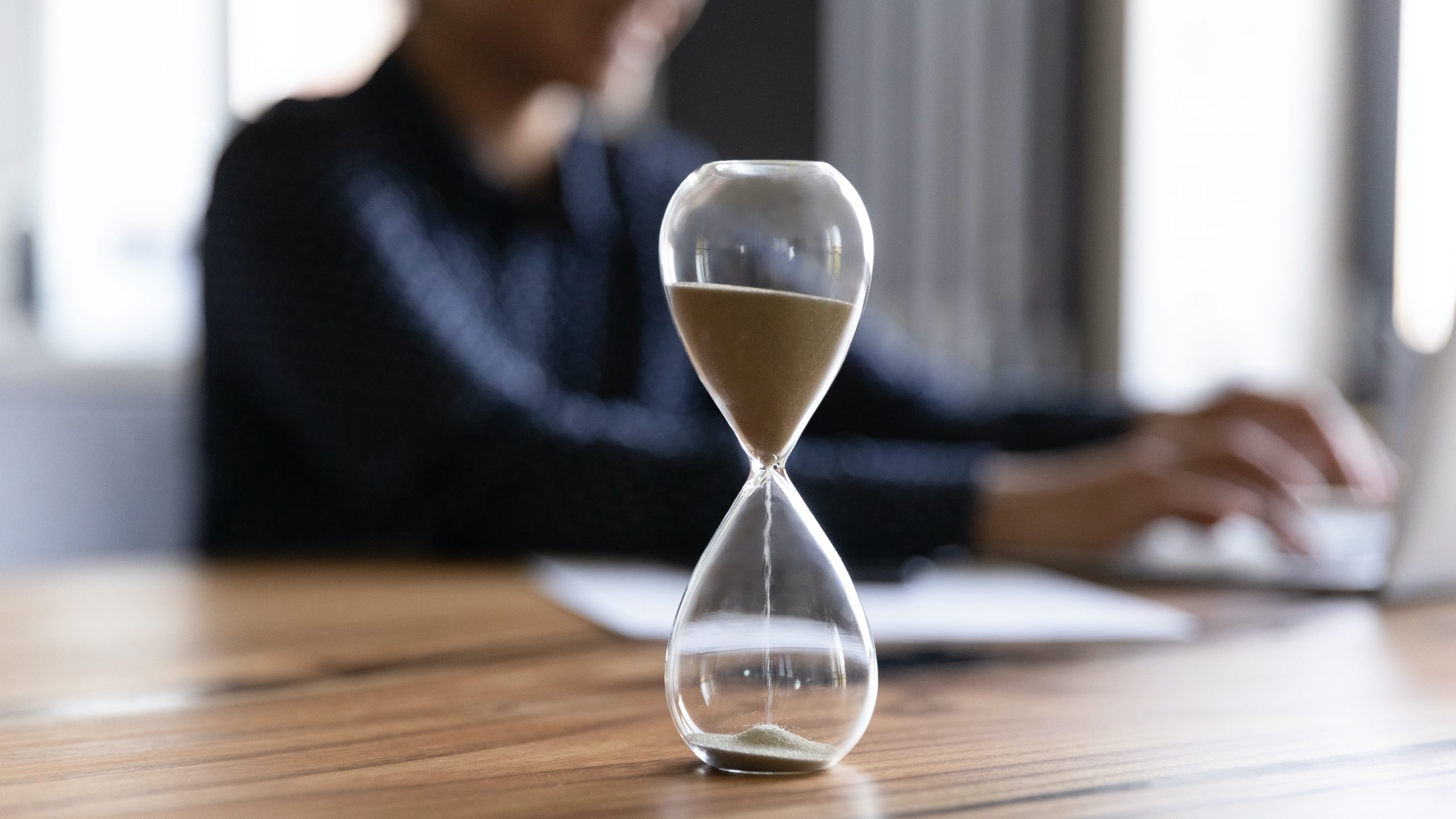 Hourglass on desk, less time concept