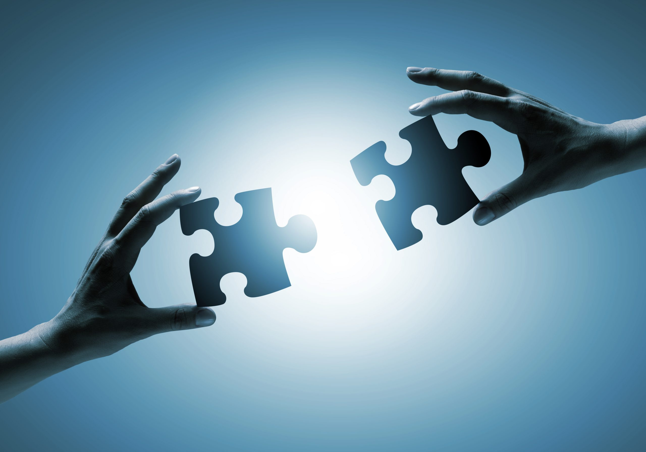 two hands with puzzle pieces that fit